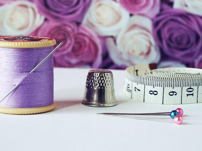 spool-of-purple-thread-near-needle-thimble-and-measuring-1266139